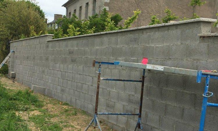 Construction du mur en agglomérés creux de 20 sur fondation béton